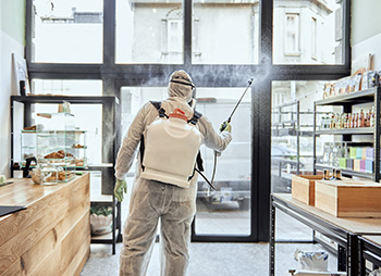 man in full body protective gear spraying the inside of a retail store