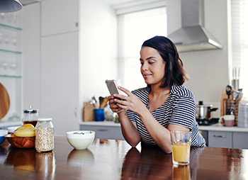 Woman at home leaning on kitchen counter checking phone