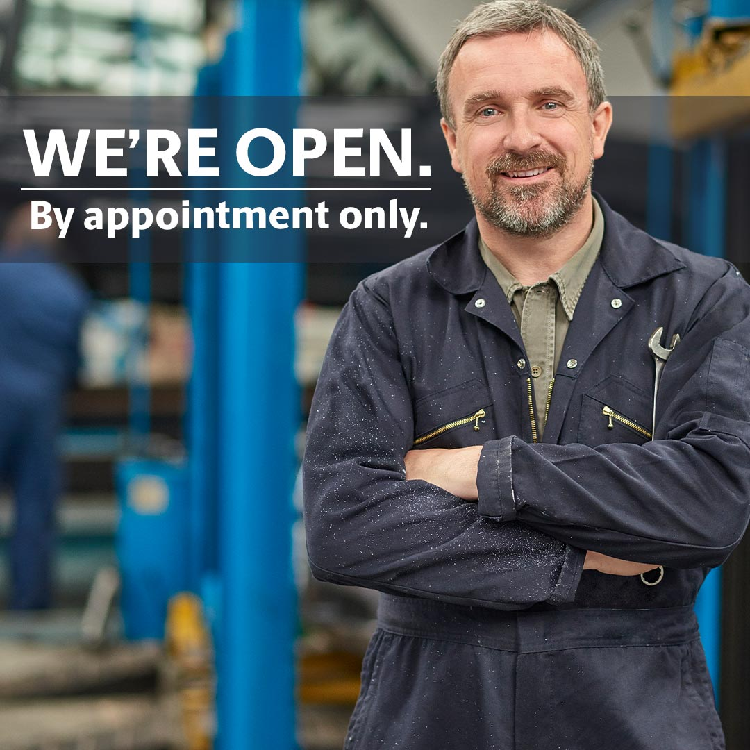 Mechanic standing next to a sign reading We are open by appointment only