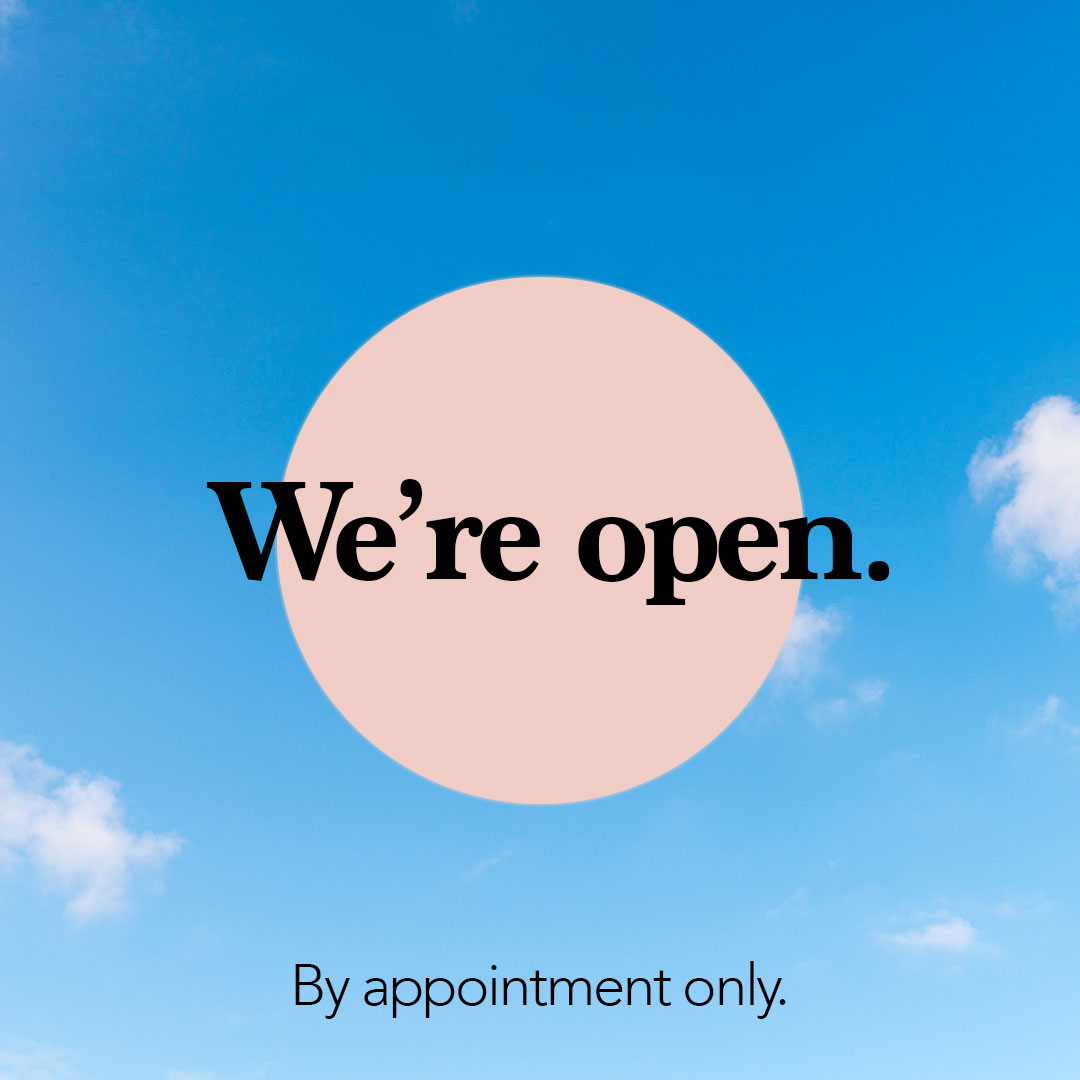 Sign stating We're open by appointment only against a blue sky
