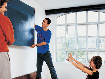 2 men centering painting with help of woman