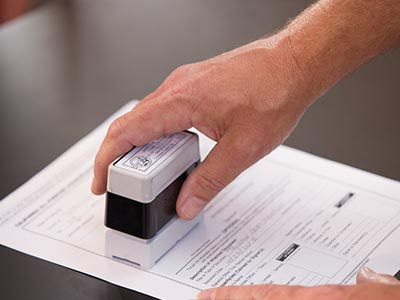 Notary applying stamp to a document
