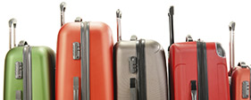Five brightly colored pieces of luggage in a row