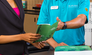 The UPS Store employee showing a green brochure to customer.