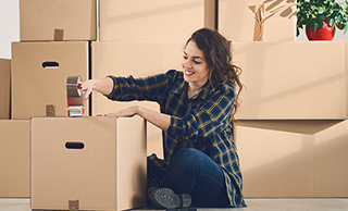 young woman taping a box in a room full of boxes