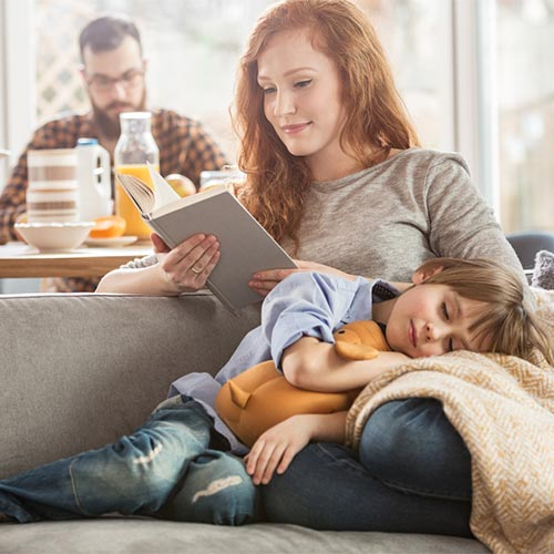 Relaxed mother with a napping son on her lap while she reads a book