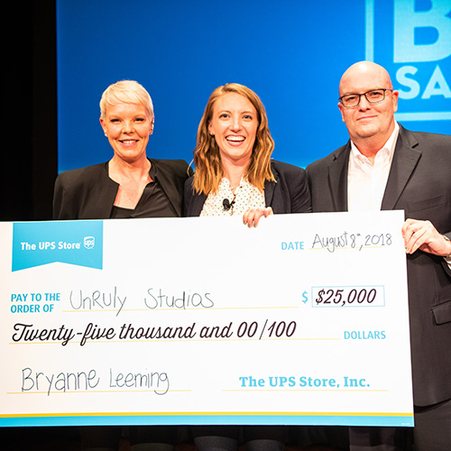 TV personality Tabatha Coffey and The UPS Store President Tim Davis hand the $25,000 grand prize check to Small Biz Salute winner Bryanne Leeming, founder and CEO of Unruly Studios.