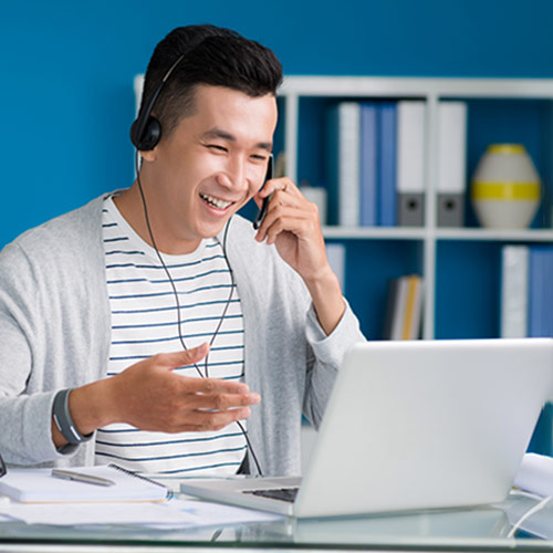 Smiling young man talking on the phone while using his laptop