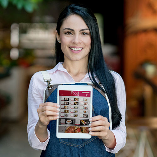 Female business owner holding an iPad with marketing images of food