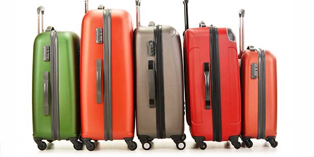 several different colored suitcases lined up.