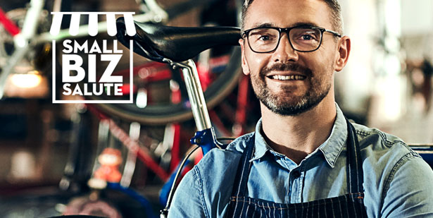 small biz salue icon embedded on an picture of a bike shop owner standing in front of store