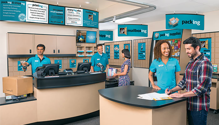 Photo of the interior of a The UPS Store, with employees assisting customers