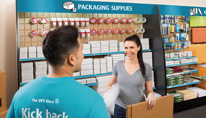 customer buying moving supplies in from of packing supplies shelving