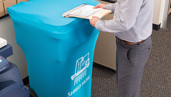 person placing documents into shredding bin with blue shroud