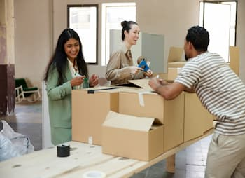 women at counter helping man box packages