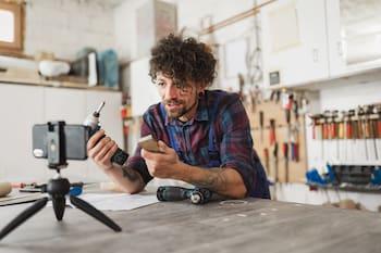 man in workshop phone on tripod