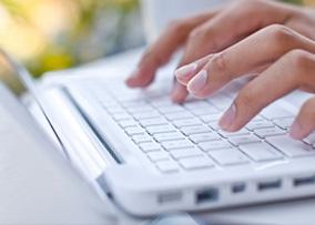 Hands typing a sleek keyboard