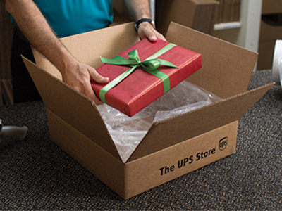 Male associate packing a wrapped gift box