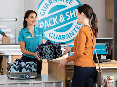 Customer handing gifts to associate for shipment