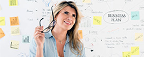 Woman brainstorming strategy on a whiteboard