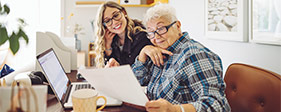 Elderly woman and younger woman doing taxes on a laptop