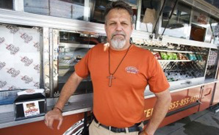 Smiling man standing in front of a food truck