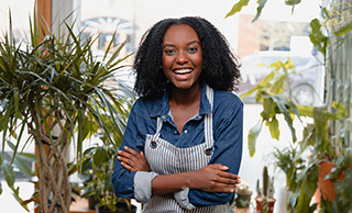 Female business owner smiling in front of hanging plants