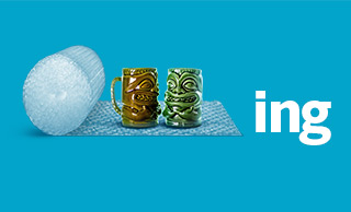 Two ceramic mugs with tiki statue designs being wrapped in bubble wrap, all on a blue background next to the letters ING.