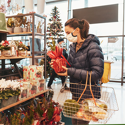 Woman with mask shopping for a small potted plant inside of a store
