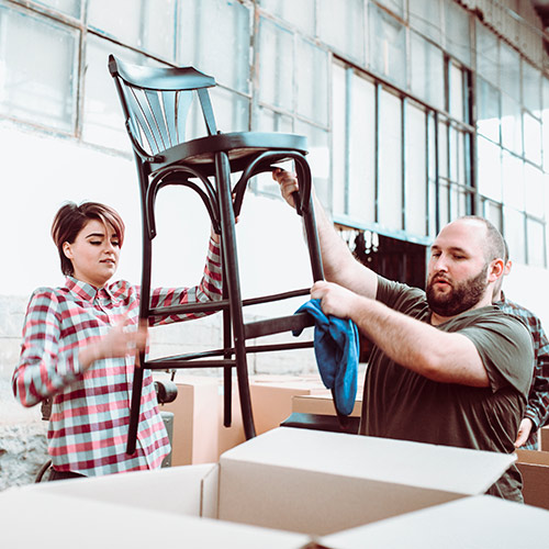Man and woman packing chair for shipment
