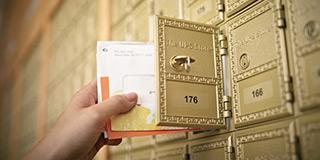 primer plano de una mano sacando correo de una casilla de correo