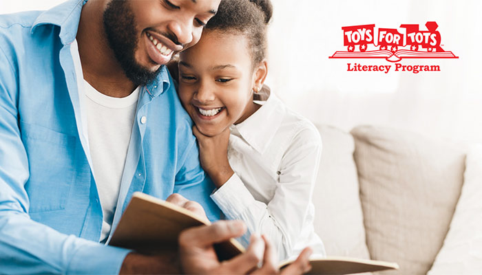 Image of a Black father smiling and reading with his daughter.
